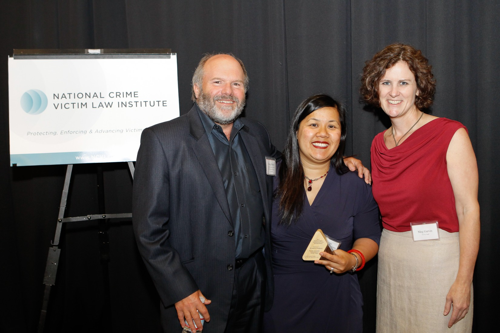 Chanpone Sinlapasai, J.D. was the recipient of NCVLI's 2013 Gail Burns-Smith Excellence in Victim Services Award for her tireless efforts advocating on behalf of crime victims in Oregon and beyond.  From left: NCVLI Founder, NCVLI Board of Directors Member, and Lewis & Clark Law Professor Doug Beloof; Chanpone Sinlapasai; NCVLI Executive Director and Clinical Professor Law at Lewis & Clark Law School Meg Garvin.