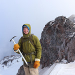 Man with ice axe on top of a mountain