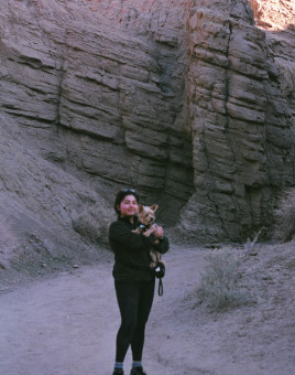 Woman in a canyon, holding a cute dog