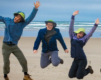 Image shows 5 people on the beach, jumping for joy