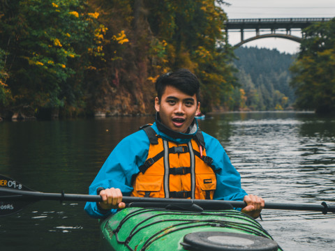 Picture shows a man wearing a blue jacket and yellow life-jacket sitting in a green kayak in the ...