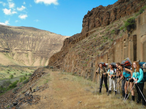 Image shows five backpackers on the bottom right of the image on a trail with columnar basalt cli...