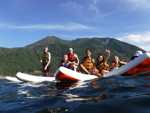 Image shows six people grouped together in PFDs sitting on stand-up paddleboards on a lake. There...
