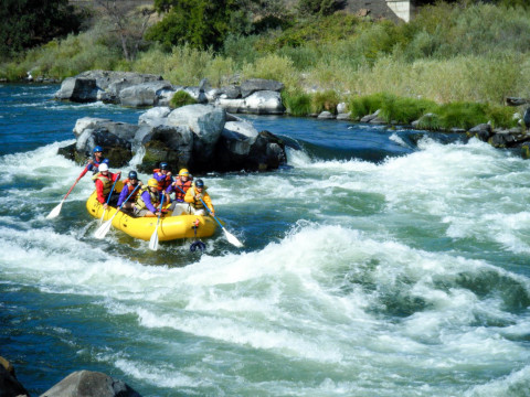 Image shows a yellow raft on the left side of the image entering a rapid on the white waters of t...
