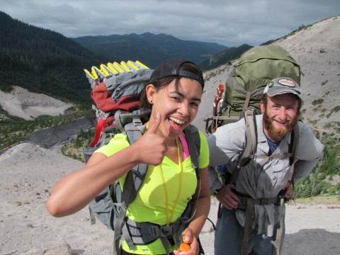 Image shows a person wearing a backpacking pack and a bright yellow shirt giving thumbs up to the...