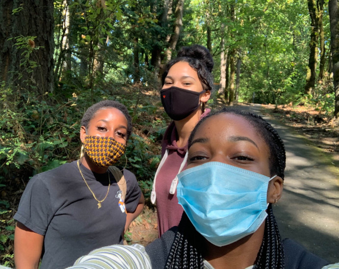 Three people show off their masks during a forest hike. We can tell they are smiling with their e...