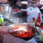 Students sauté red peppers in a pan over a camp stove outdoors.