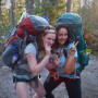 "Two women wearing backpacking packs give the ""peace"" sign"