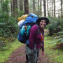 Person with a backpacking pack on a hiking trail in the forest