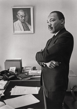 Martin Luther King Jr. in his SCLC office. On the wall is a portrait of Mahatma Gandhi, whose practice and teaching of nonviolent direct action inspired King's work. King asked Bob Fitch to photograph him here for the jacket of his then-forthcoming (and last) book, Where Do We Go From Here? published in 1967. This image is also the basis for the Martin Luther King Jr. Memorial in Washington, D.C., unveiled in 2011. Atlanta, Georgia, 1966.