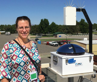 Assistant Professor Jessica Kleiss with a TSI, which captures images of the sky every 30 seconds.