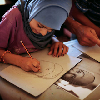 A young artist in the Zaatari refugee camp, Jordan (Photo by Samantha Robison BA '08)