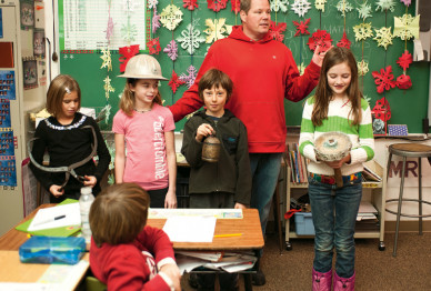 Clay Warburton B.A. '92, a fourth-grade teacher at Sisters Elementary School, uses artifacts fr...