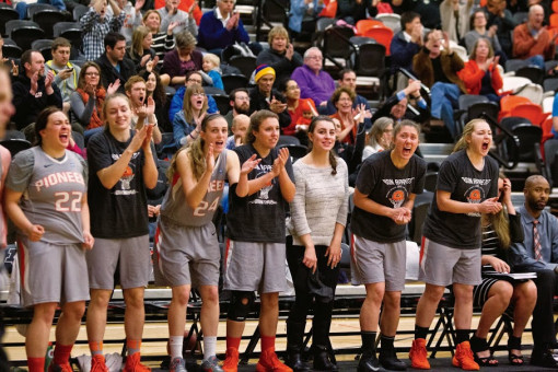 An enthusiastic crowd cheers on the women's basketball team.