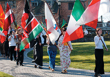 A diverse group of Lewis & Clark students carry colorful flags from several countries: international students wearing the native attire of their home countries; American students who have lived abroad; and Third Culture Kids, U.S. and non-U.S. citizens who have grown up overseas or lived overseas for a significant amount of time.