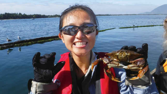 A student from Professor Nilsen's trip shows off her prize catch of a Dungeness crab. (College Outdoors)