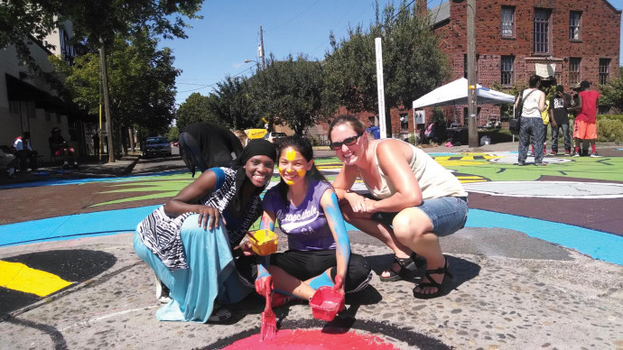 Kallie Kurtz (far right) works with teens painting a street mural for peace.