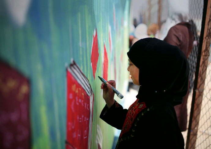 A young Syrian refugee paints a street mural as part of an aptART workshop in the Zaatari refugee...