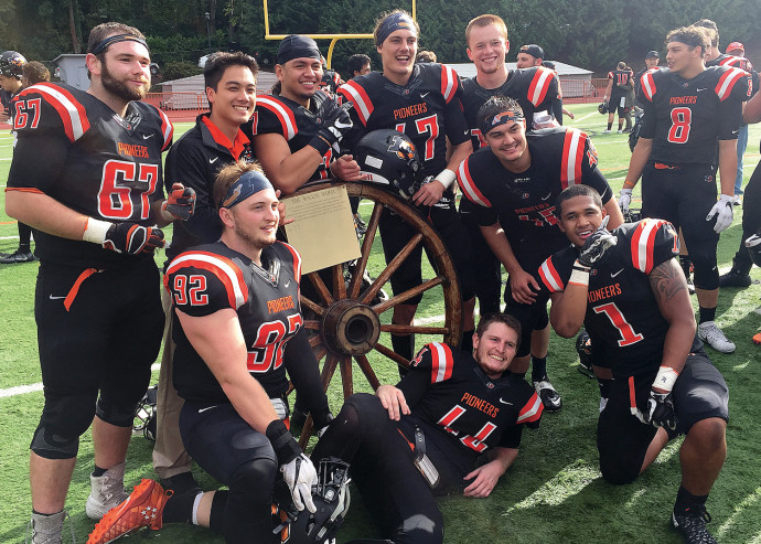 After beating Willamette, several seniors pose with the Wagon Wheel traveling trophy. (lcpioneers.com)