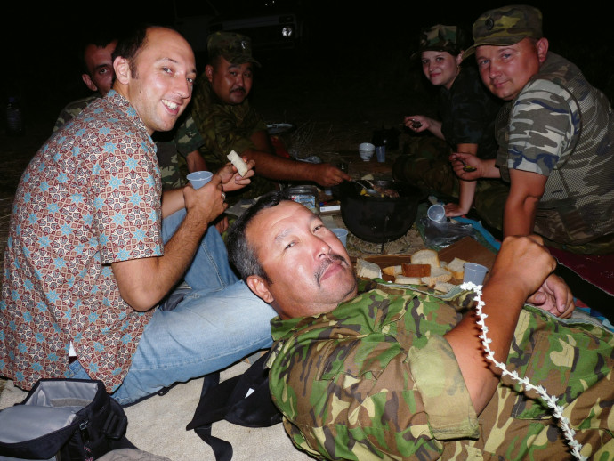 Carl Schreck B.A. '98 eating wild rabbit stew with officers from the Interior Ministry of Kazakhstan; they were taking a break from tracking cannabis smugglers.