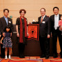 The families of Kei Nagai B.A. '97 (left) and Toshinobu Toyama B.A. '97 (right) join Betsy Am...