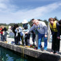 Erik Nilsen, associate professor of psychology, shows students how to bait a crab pot during a cr...