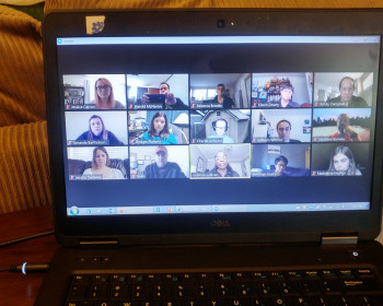 Image depicts a laptop. Three rows of faces show students and staff engaged in a Zoom call.