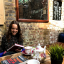 Sarit Cahana BA '20 sitting on the left side of the photo at a table containing books, tea set,...