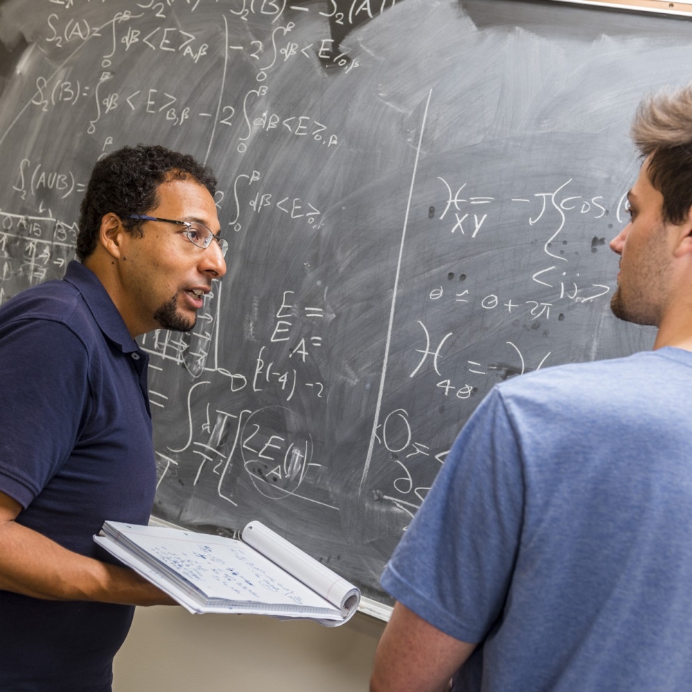Physics professor Mohamed Anber and physics major Ben Kolligs '18 work through a theoretical ...