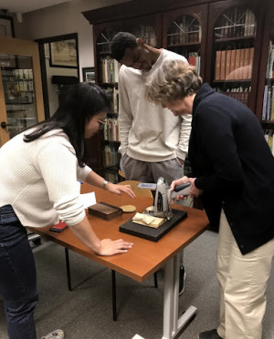 Camille Wong BA '19, Jonathan Boddie BA '18, and Valerie Walters examine a page in the book o...