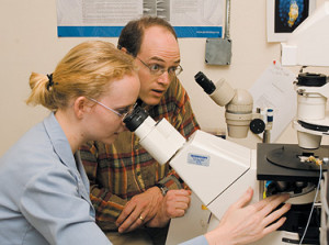 Professor of Biology Greg Hermann and Beverly Rabbitts '06 microinject a worm to alter its gene e...
