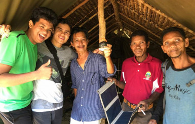 Ary Hashim BA '20 and members of the project team with equipment from the first solar installat...