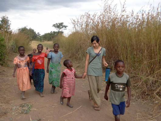 Megumi Nagata ?11 walking in Mangulu Village, Malawi. She is holding hands with her host sister, ...