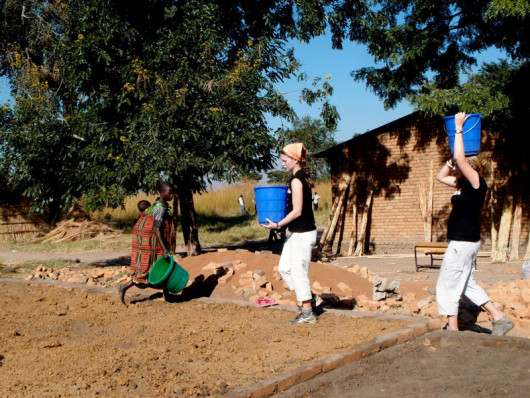 Katie Keith ?15 and Anna Lofstrand ?13 carry water from the well to the worksite to help mix cement.